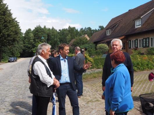Vinvent Kokert (Mitte) im Gespräch mit Anwohnern. Im Hintergrund deutlich zu erknennen die marode Pflasterstreife und der Randstreifen, auf den zum Leidwesen der Dörfler ausgewichen wird. Foto: CDU